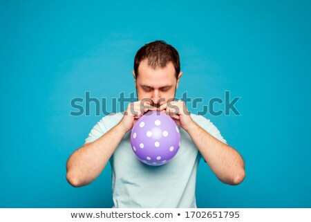 Stock photo: man trying to blow a balloon