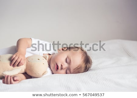 Stock photo: Baby sleeping in crib with toy teddy bear.