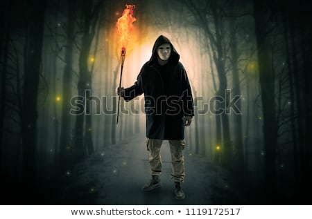 mysterious man coming from a path in the forest with glowing lantern concept stock photo © ra2studio