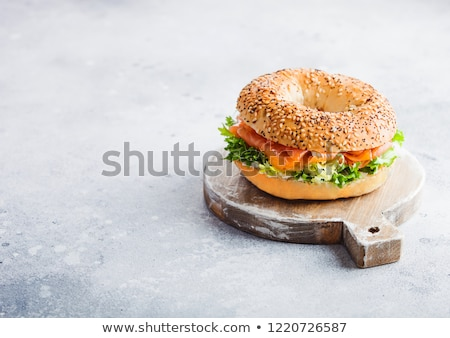 fresh healthy bagel sandwich with salmon ricotta and lettuce in grey plate on light kitchen table b stock photo © denismart