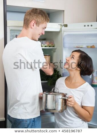 Joven búsqueda alimentos refrigerador confundirse hombre Foto stock © AndreyPopov