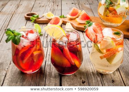 Glass of iced sangria with strawberry, orange, apple and lemon o Stock photo © dashapetrenko