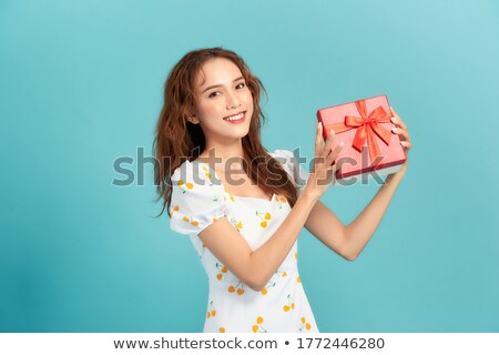 Excited asian beautiful woman isolated over blue background holding passport with tickets. Stock photo © deandrobot