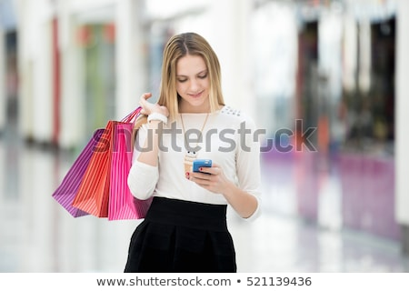 Stockfoto: Woman look at mobile phone with paperbags in the mall while enjo