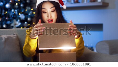 Close up portrait of an excited young woman opening present box while lying in bed at home Stock photo © ElenaBatkova