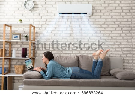 woman using laptop enjoying cooling under air conditioner stock photo © andreypopov