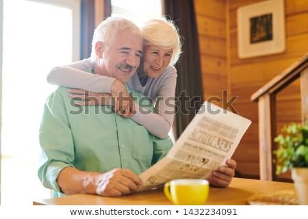 Cheerful senior couple in casualwear looking through latest news Stock photo © pressmaster