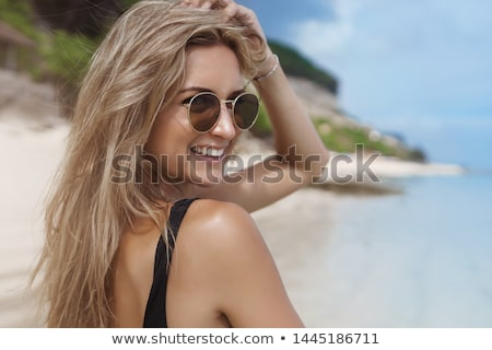 A woman near the sea with blonde hair and sunglasses walks in early autumn Stock photo © ElenaBatkova