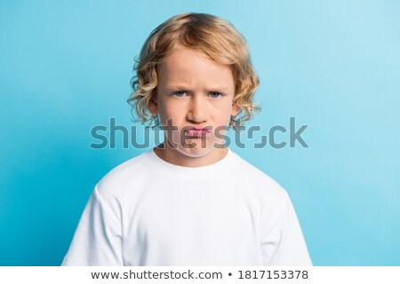 Disappointed upset man in blue shirt over t-shirt, grimacing from discomfort and dislike, cover ears Stock photo © benzoix