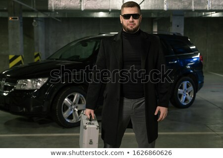 Bearded criminal or agent in black coat and sunglasses moving down parking area Stock photo © pressmaster