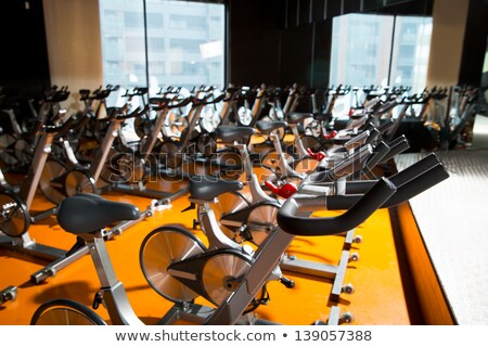 Aerobics spinning exercise bikes gym room with many in a row BANNER, LONG FORMAT Stock photo © galitskaya