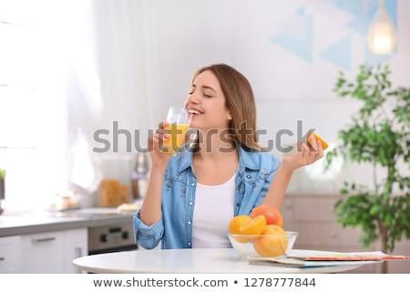 smiling woman drinking orange juice at home Stock photo © dolgachov