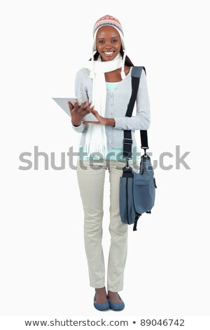 Smiling young student with hat, scarf and touchpad against a white background Stock photo © wavebreak_media