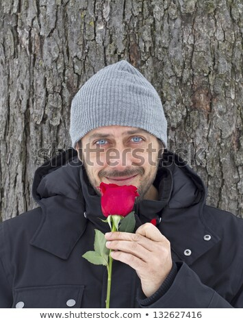Sensible man smelling flower Stock photo © curvabezier