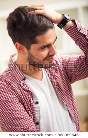 young man passes hand through hair stock photo © feedough