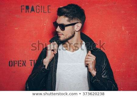 casual young man closing his leather jacket Stock photo © feedough