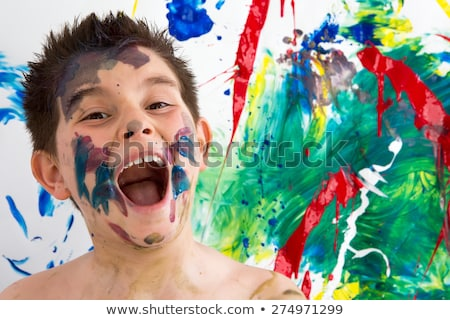 funny little boy with paint splodges on his face stock photo © ozgur