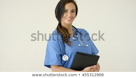 Woman in scrubs holds black portfolio and smiles Stock photo © dash