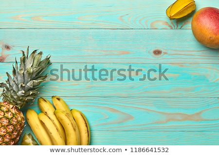 Corner frame of tropical fruits, mango, carambola and pineapple on a blue wooden background with cop Stock photo © artjazz