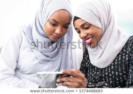 Portrait of beautiful smart young muslim woman wearing black hijab using virtual reality headset on  Stock photo © Traimak