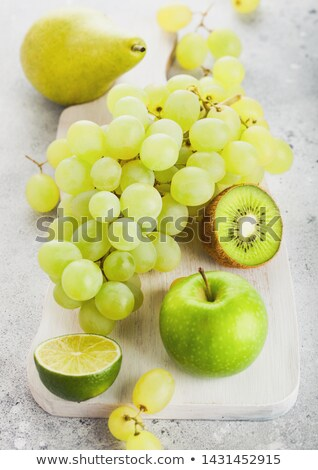 Fresh raw organic green toned fruit on white chopping board on s Stock photo © DenisMArt