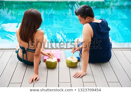 Young couple coconut cocktail near swimming pool  Stock photo © dashapetrenko