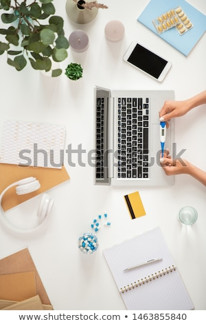 Sick human with thermometer over laptop keypad ordering medicine online Stock photo © pressmaster