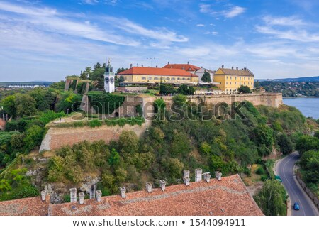 Petrovaradin clock tower and old fortress above Danube river vie Stock photo © xbrchx