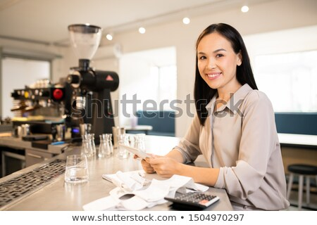 Young successful manager or accountant of restaurant counting earnings Stock photo © pressmaster