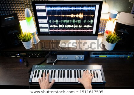 Piano keyboard and computer screen with waveform sound visualization on desk Stock photo © pressmaster
