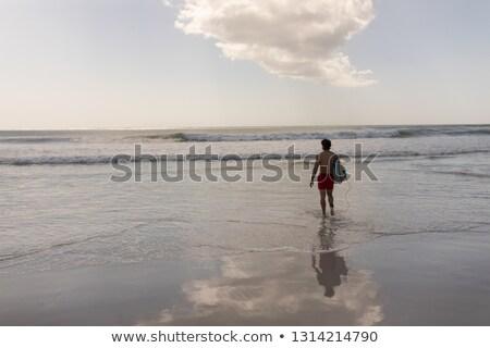 Vista posteriore a torso nudo giovani maschio surfer tavola da surf Foto d'archivio © wavebreak_media