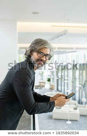 Successful businessman in formalwear scrolling in smartphone for contact Stock photo © pressmaster