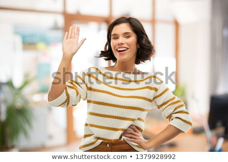 smiling woman in striped pullover waving hand Stock photo © dolgachov