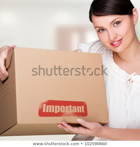 A woman holding a box inside office building or home interior. P stock photo © HASLOO