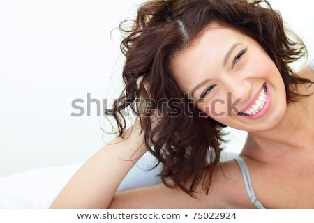 Smiling woman lying on bed in black and white stock photo © konradbak