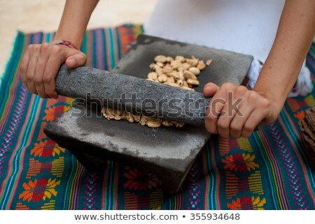 Grinding cocoa beans in the mortar Stock photo © pzaxe