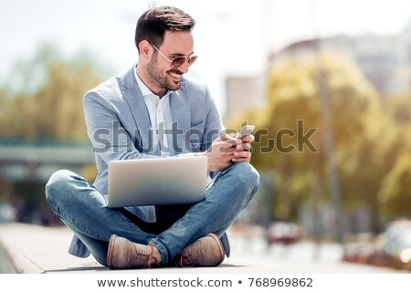 young man looking down while sitting stock photo © feedough