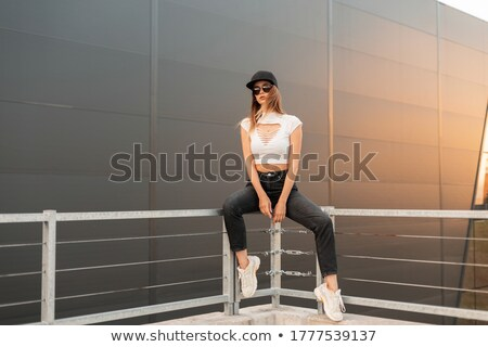 Young Woman in Baseball Cap and Sneakers Stock photo © gromovataya