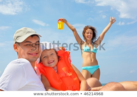 young man with little girl in orange lifejacket on beach Stock photo © Paha_L