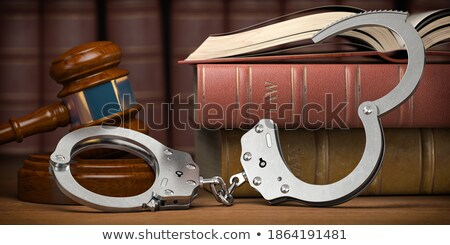 Handcuffs on wooden table. 3D illustration Stock photo © ISerg