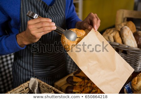 Stock photo: Staff packing a croissant in paper bag at counter