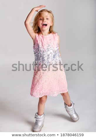 Charming young girl in pink dress on gray background. Cheerful girl in square glasses. The girl put  Stock photo © Traimak