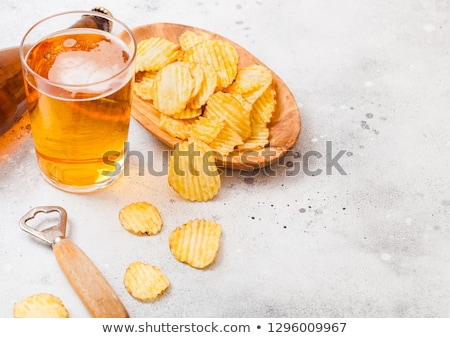 Glass of lager beer with potato crisps snack on stone board on black background. Beer and snack Stock photo © DenisMArt