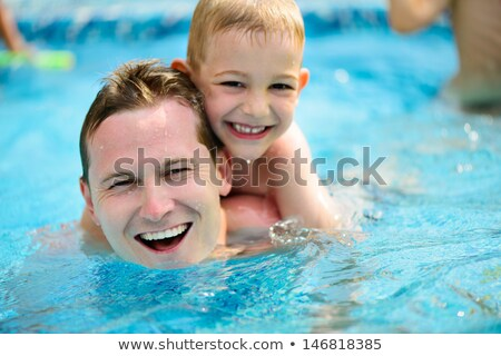 portrait of cheerful kids and parents swimming in pool with pink stock photo © deandrobot