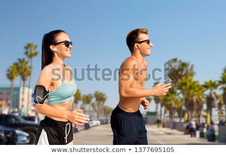 couple with earphones running over venice beach Stock photo © dolgachov