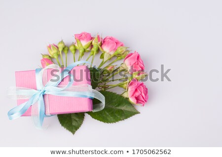 Bouquet of white roses with red bow on blue background. Boxed gift on side Stock photo © dash