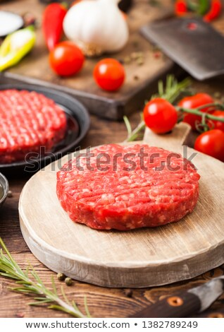Fresh raw minced homemade farmers grill beef burger on round chopping board with spices and herbs an Stock photo © DenisMArt