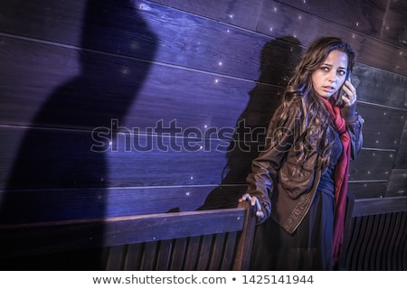 Scared Young Adult Woman Uses Cell Phone As Mysterious Male Shad Stock photo © feverpitch