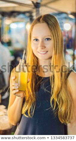 Woman drinking sugar cane juice on the Asian market VERTICAL FORMAT for Instagram mobile story or st Stock photo © galitskaya