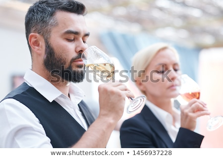 Young bearded male sommelier and his female colleague smelling new sorts of wine Stock photo © pressmaster